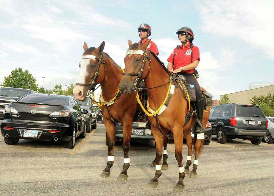 DAVID HOPPER: FOR THE CHRONICLE ON PATROL: Cpl. Curtis Hillard, left, and Trooper First Class Lori Williamson, both with Alpha & Omega Mounted Security Patrol, ride their horses, J.J. and Sully, as they patrol The Woodlands Mall parking lot. Photo: David Hopper / freelance