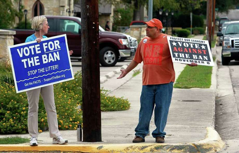 Linda Dickerson and David Martinez carry on their morning long conversation at St. Paul Lutheran Church polling station as New Braunfels citizens go to the polls to vote in the can ban issue  on November 8, 2011. Dickerson admitted that the two were both interested in keeping the local rivers clean. Photo: TOM REEL, SAN ANTONIO EXPRESS-NEWS / © 2011 San Antonio Express-News