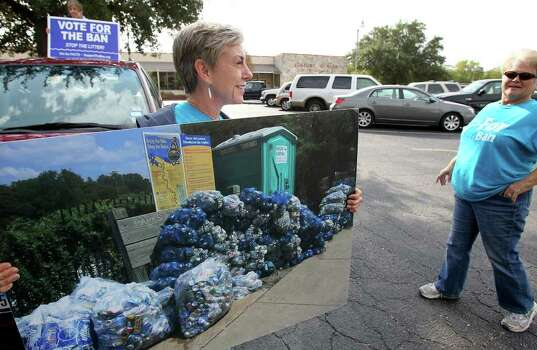 METRO  Valin Miller holds an enlarged picture of cans collected from the river as Toni Peters looks on at the Comal County Senior Citizens Center, polling station for precinct 101, as New Braunfels citizens go to the polls to vote in the can ban issue  on November 8, 2011.  Tom Reel/Staff Photo: TOM REEL, SAN ANTONIO EXPRESS-NEWS / © 2011 San Antonio Express-News