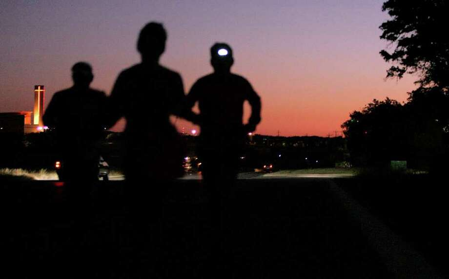 A group of runners travels on Loop 1604 against a breaking dawn. Thirteen organ transplant recipients will run or walk in the Rock 'n' Roll San Antonio Half-Marathon on Sunday. Photo: MICHAEL MILLER, SAN ANTONIO EXPRESS-NEWS / mmiller@express-news.net