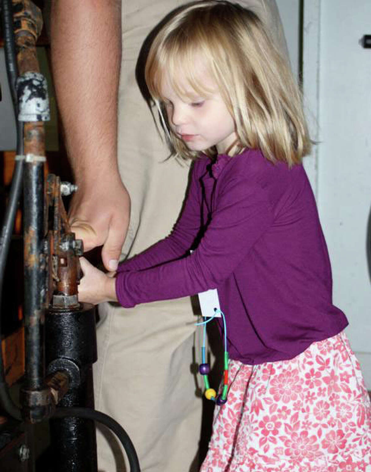 SMNS student Chloe Perkins gives the old-fashioned cider press a try.