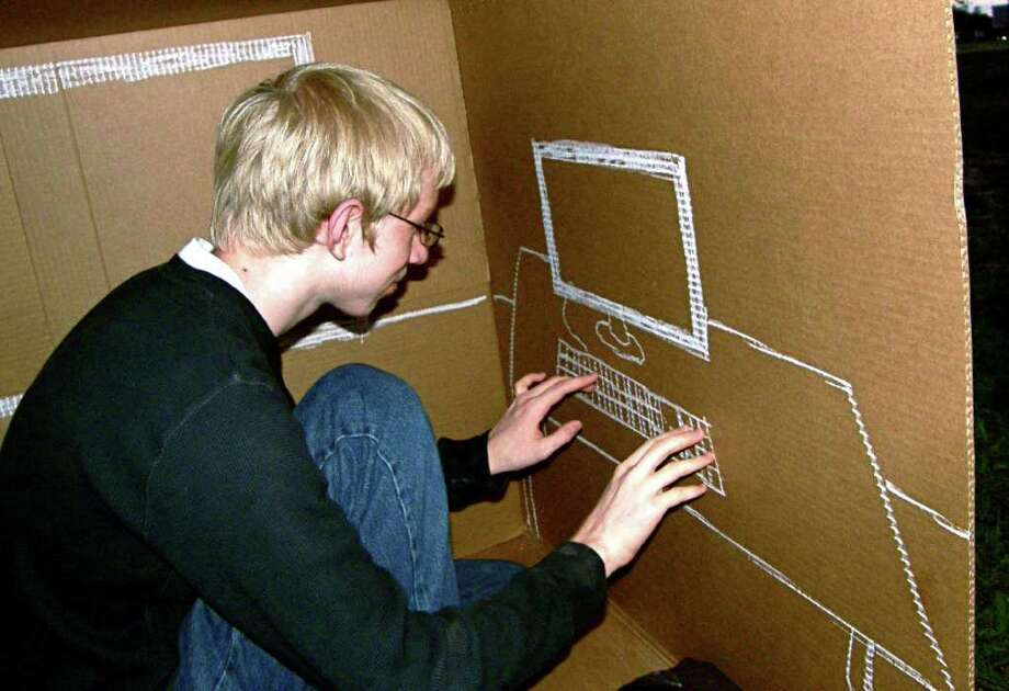 NOT LIKE HOME: Berry Miller Junior High eighth-grader Gabe Richardson, 14, pretends to type on a computer he drew with chalk on his cardboard box. Although he missed the comforts of home, he said he recognizes the need to draw attention to homelessness. Photo: Rachael Gleason