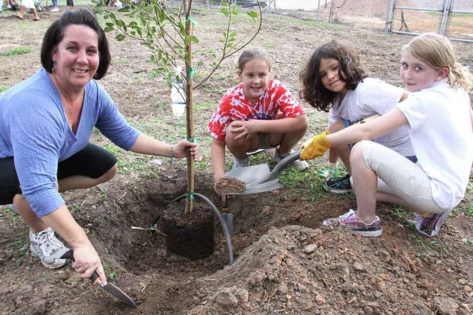 SUZANNE REHAK: FOR THE CHRONICLE TAKING ROOT: From left, Kim Lybarger, a fourth-grade teacher at Jane Long Elementary in Richmond, plants a plum tree with students Elizabeth Anders, Gabriella Linares and Ashley Banfield at the Calvary Episcopal Church community garden at 207 N. Seventh Street in Richmond. Photo: Suzanne Rehak