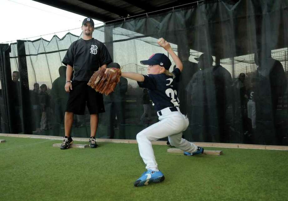 Houston Banditos Coach Rocky Hughes, left, of Houston, helps Russian youth baseball team member Ivan Moiseev, 9, with his pitching motion during a training session at Ray Deleon's Banditos Baseball Training Center in Tomball. Freelance photo by Jerry Baker Photo: Jerry Baker