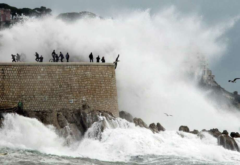 People look at high waves on November 8, 2011 in the southern French city of Nice. Heavy rain and flooding hit southern France at the weekend, seeing hundreds of people evacuated, three killed in flood-related accidents. In Var, one of the worst-hit regions, more than 1,600 people were evacuated or assisted by authorities and about 3,900 homes were without electricity. Photo: VALERY HACHE, Getty / AFP