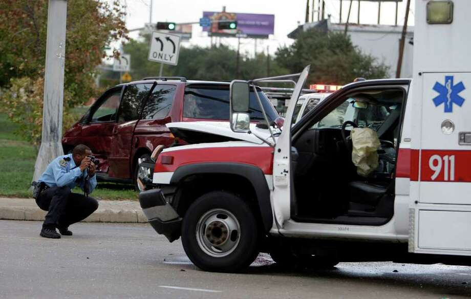 A Houston Police Officer takes photographs during the investigation at the scene of an accident involving a Houston Fire Department ambulance and a mini-van at the the intersection of Pease and Chartres, two HFD firefighters were transported to a hospital with minor injuries Tuesday, Nov. 8, 2011, in Houston. Photo: James Nielsen, Chronicle / © 2011 Houston Chronicle