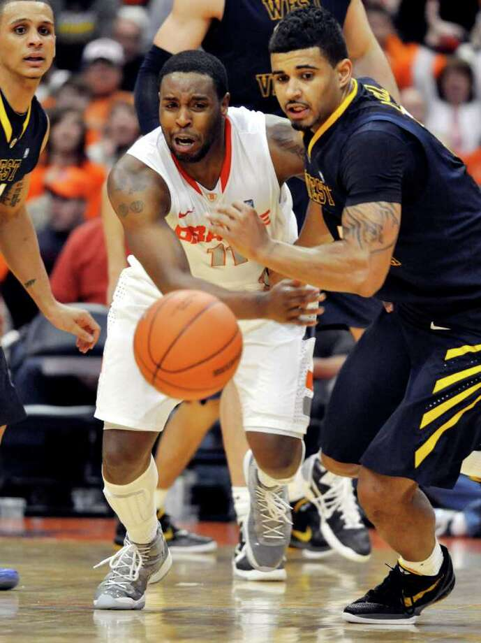 Syracuse's Scoop Jardin, center, and West Virginia's Casey Mithcell chase a loose ball as Joe Mazzulla, left, looks on during the second half of an NCAA college basketball game in Syracuse, N.Y., Monday, Feb. 14, 2011. Syracuse won 63-52. Photo: Kevin Rivoli/Associated Press / AP2011