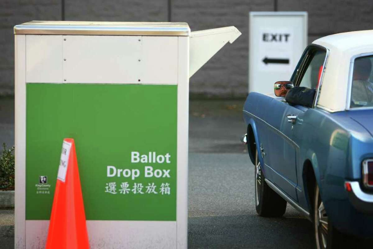 A voter drops a ballot on Tuesday, November 8, 2011 at the King County Elections facility in Renton.