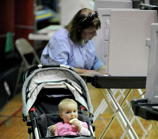 Samarpana Tamm casts her ballot on election day at New Lebanon School in Byram Tuesday afternoon, Nov. 8, 2011, as her granddaughter, Nadira Dietz, 1, munches away on a cookie, Photo: Bob Luckey / Greenwich Time