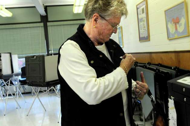 Sigrid Bray fixes a sticker showing she voted on her jacket at the District 8 polling station Central Middle School Tuesday, Nov. 8. 2011. Photo: Helen Neafsey / Greenwich Time