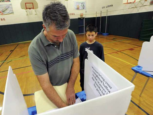 Tim Delollo of Colonie fills out a ballot as his son Joseph, 11, waits patiently on Election Day at Forts Ferry Elementary School in Colonie, N.Y. on Tuesday, Nov. 7, 2011. (Lori Van Buren / Times Union) Photo: Lori Van Buren