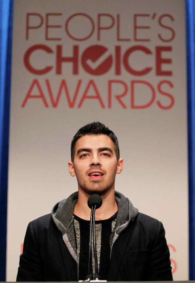 Musician Joe Jonas peaks during the nominations announcement for People's Choice Awards 2012, Tuesday, Nov. 8, 2011, in Beverly Hills, Calif.  The People's Choice Awards 2012 will be held Jan. 11, 2012. (AP Photo/Matt Sayles) Photo: Matt Sayles, STF / AP