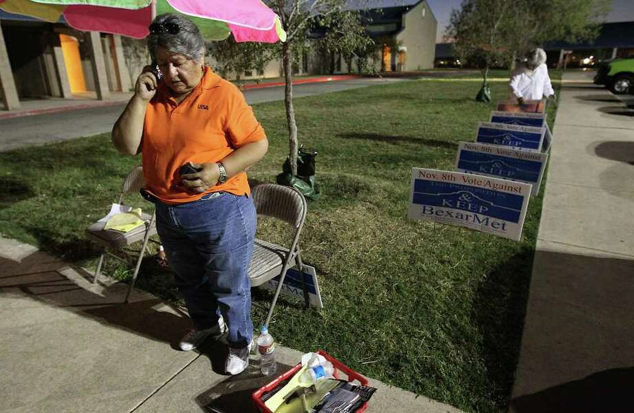 BexarMet Water District Board President Guadalupe Lopez works the phones while at the Carrillo Elementary poll site on Tuesday, Nov. 8, 2011. Voters decided whether to keep or dissolve the water district which services residents that are not with San Antonio Water System. The BexarMet board has been in a center of controversy and alleged corruption for the past several years. Kin Man Hui/kmhui@express-news.net Photo: Kin Man Hui, SAN ANTONIO EXPRESS-NEWS / San Antonio Express-News
