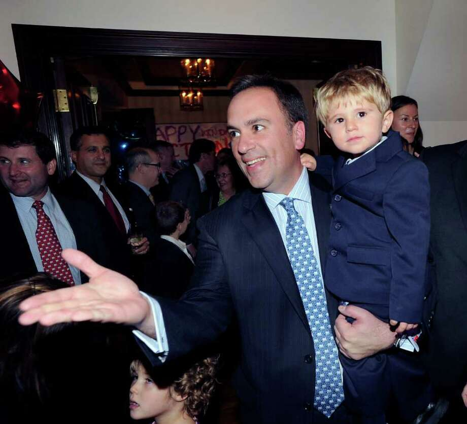 Greenwich First Selectman Peter Tesei, holds his son, James, 2, as he celebrates his election victory at the Milbrook Club, Greenwich, Tuesday night, Nov. 8, 2011. Photo: Bob Luckey / Greenwich Time