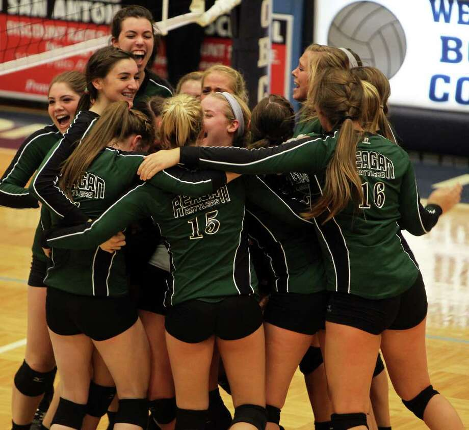 Reagan volleyball players celebrate their 16-25, 29-27, 25-22, 20-25, 15-11 victory against New Braunfels in a Class 5A third-round contest Tuesday night, Nov. 8, 2011, at South San High School's Durbon Center. Photo: Jennifer Whitney, Special To The Express-News / Jennifer Whitney/special to the Express-News