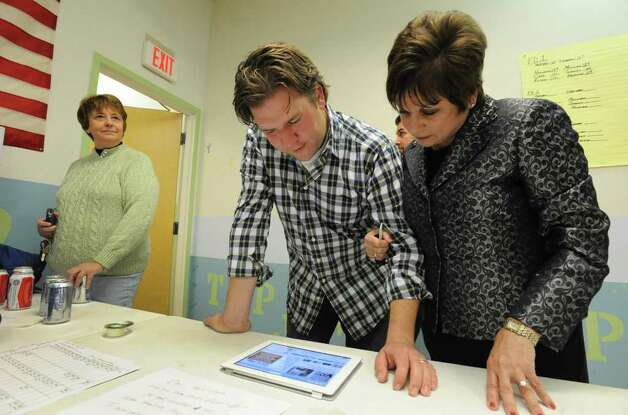 Colonie Town Supervisor Paula Mahan, right, checks results on an iPad with friend Peter Gannon of Loudonville as she gathers with supporters in Colonie, N.Y. on Tuesday, Nov. 7, 2011. Jean Donovan of Colonie looks on at right. (Lori Van Buren / Times Union) Photo: Lori Van Buren