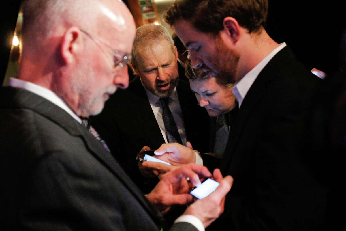 Seattle Mayor Mike McGinn and other city officials check election return results for a $232 million Seattle education levy on their smart phones at the Elysian Fields restaurant in Seattle.