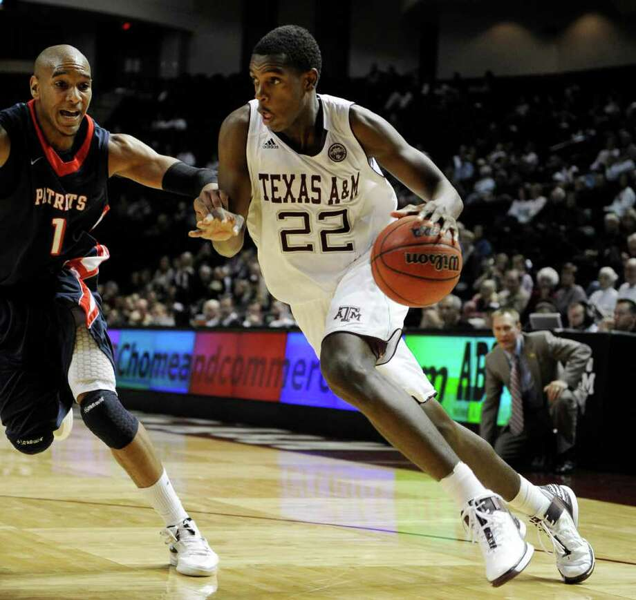 Texas A&M forward Khris Middleton (22) drives the ball around Dallas Baptist forward Jordan McGowen (1) during the first half of an NCAA college exhibition basketball game on Thursday, Nov. 3, 2011, in College Station, Texas. (AP Photo/Pat Sullivan) Photo: Pat Sullivan, Associated Press / AP