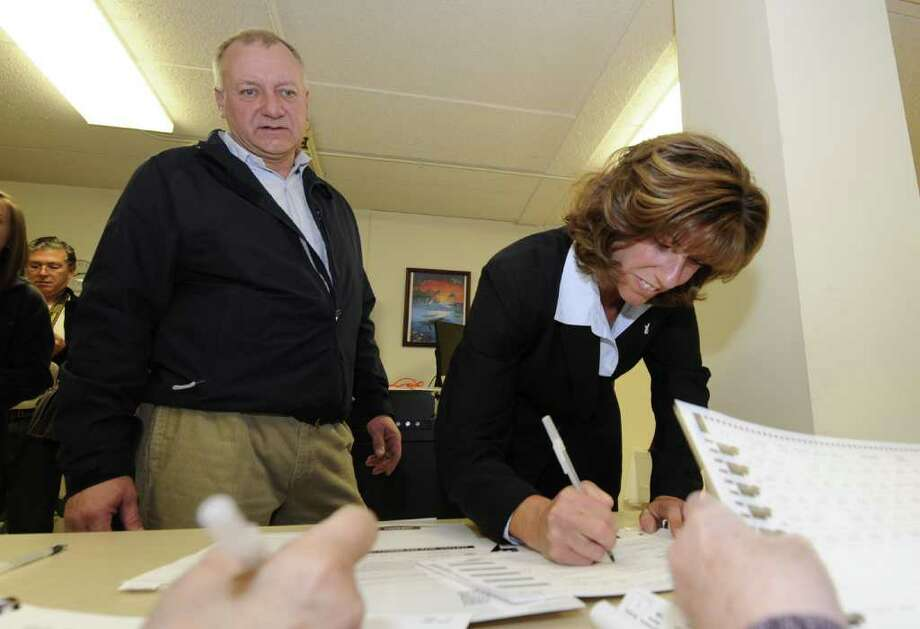 Carmella Mantello accompanied by her husband Paul Laviano signs in at the poling place at the Conway Court Apartments in Troy, N.Y. November 8, 2011.    (Skip Dickstein/Times Union) Photo: Skip Dickstein / 00015293A