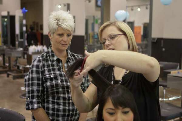 R. CLAYTON MCKEE: FOR THE CHRONICLE A LEARNING EXPERIENCE: Cathy Bradley, left, watches student Brooke Cavanagy practice on model Vanessa Fernandez.  Bradley is in the process of becoming a cosmetology instructor at Paul Mitchell School.