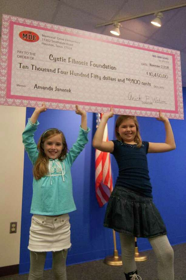 R. CLAYTON MCKEE: FOR THE CHRONICLE A WHOLE LOT OF WALKING: Pupils at Memorial Drive Elementary School walked 9,115 laps to raise $10,450 for the Cystic Fibrosis Foundation. Participants, second grader Amanda Janecek, 7, and her sister, fifth grader Caroline Janecek, 10, display the check, presented to the foundation during morning announcements at the school. Photo: R. Clayton McKee / © R. Clayton McKee