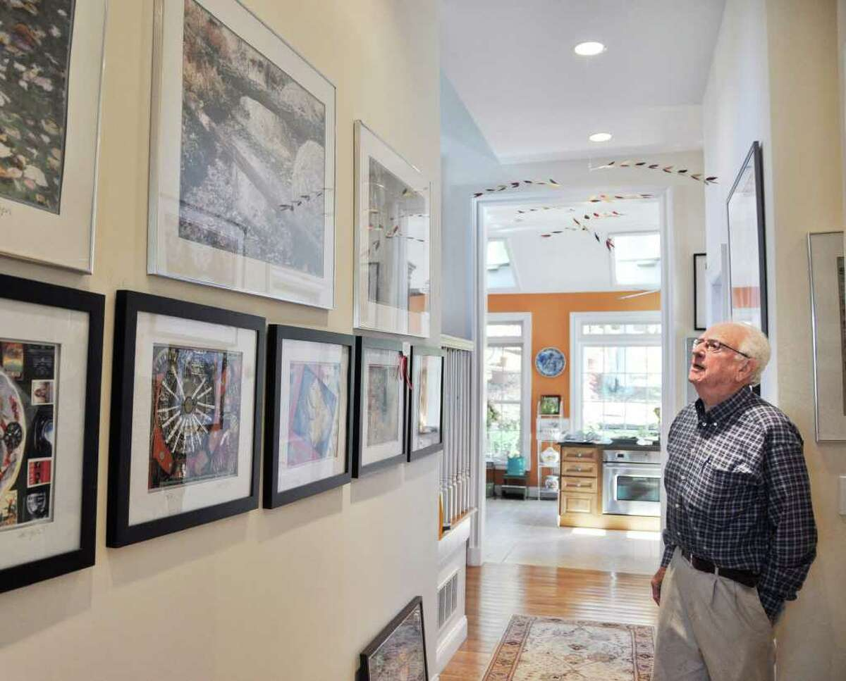 Irwin Berger stands in the hallway of his home where many of his artworks are displayed. This photo was taken on Wednesday, November 9, 2011.
