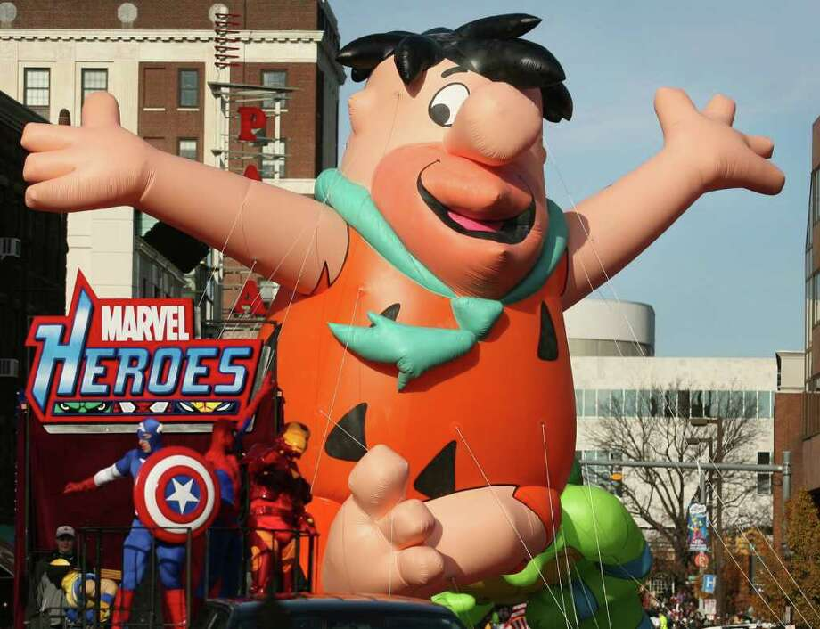 Fred Flintstone, seen here flying high during last year's UBS Parade Spectacular, will return this year, along with nearly two dozen other giant balloons, marching bands, floats, dancers and other performers and hundreds of volunteers. The parade kicks off Sunday, Nov. 20, at noon in downtown Stamford. A parade inflation party is set for Saturday, Nov. 19, from 3-6 p.m. Photo: Staff File Photo / Connecticut Post