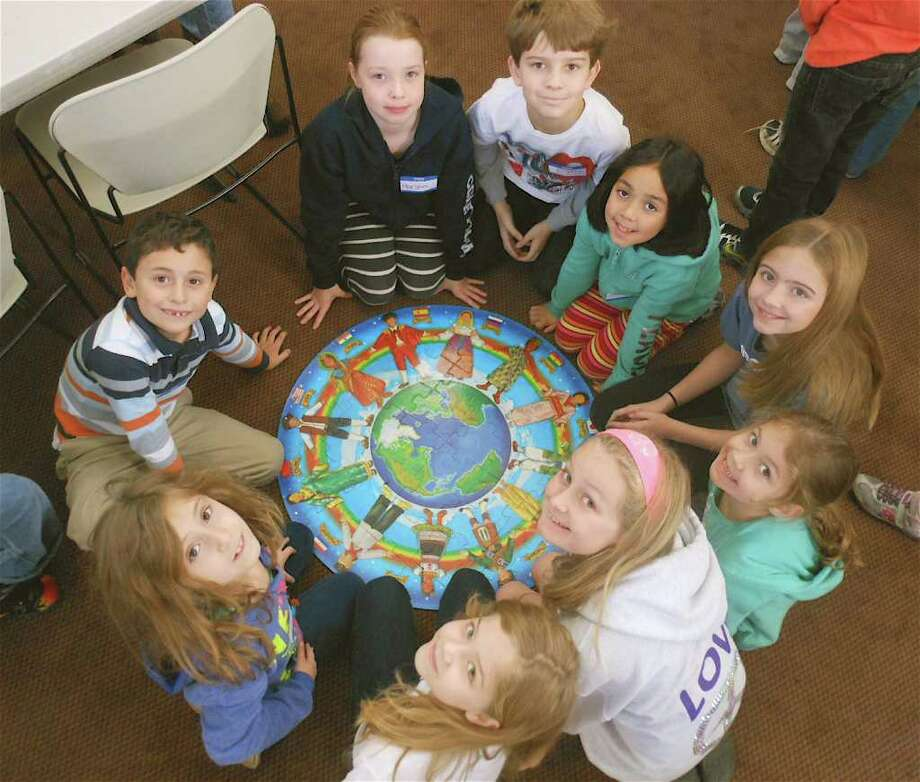 Youngsters in the Westport Historical Society's Election Day Kids Program on Tuesday completed a puzzle together showing different children from around the world. Photo: Mike Lauterborn / Westport News contributed