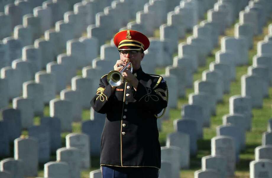 """A bugler plays """"Taps"""" during the group burial service of Army Capt. Arnold E. Holm Jr. of Waterford, Connecticut, Spc. Robin R. Yeakley of South Bend, Indiana, and Pfc. Wayne Bibbs of Chicago, who were missing in action from the Vietnam War, at Arlington National Cemetery November 9, 2011 in Arlington, Virginia. The remains of the three servicemen have been indentified and being returned to their families for burial. Photo: Alex Wong, Getty / 2011 Getty Images"""