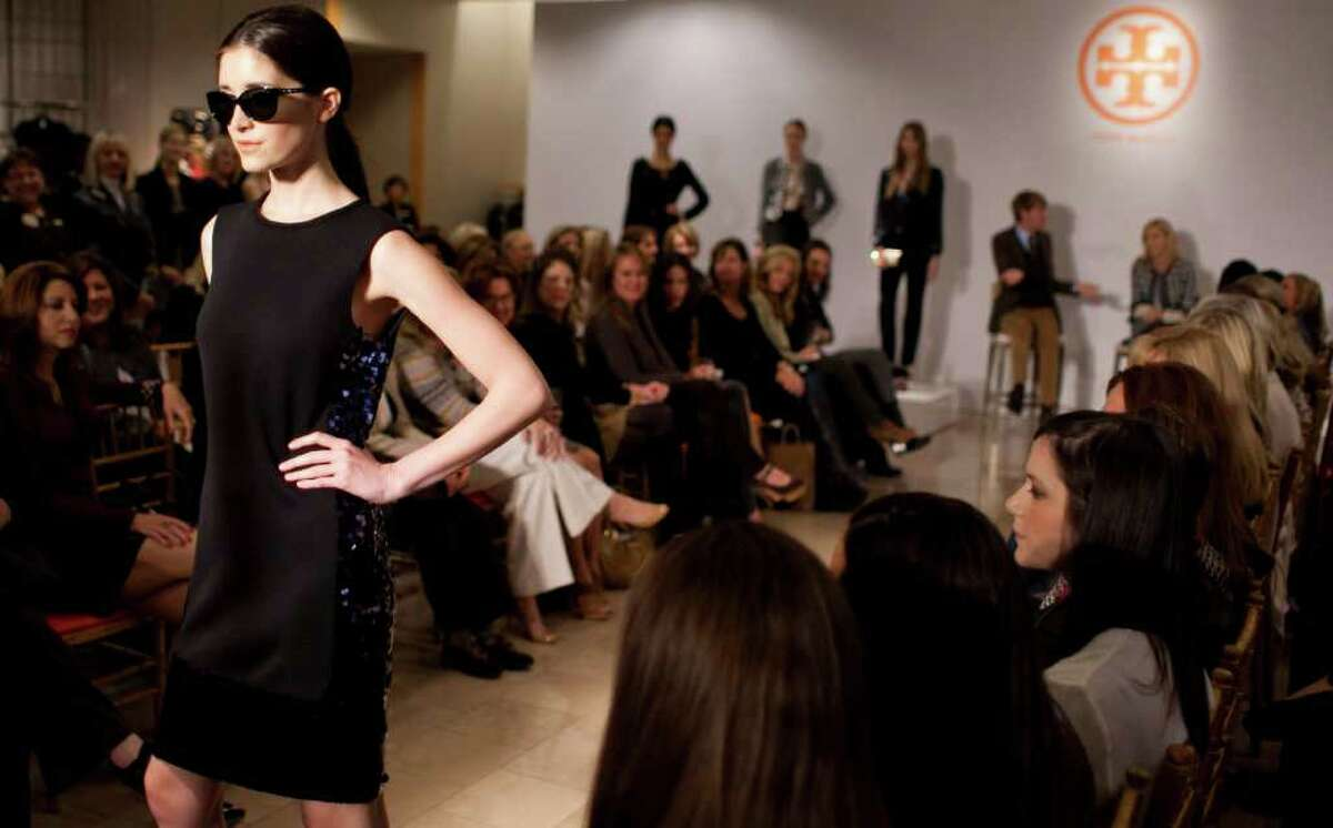 Models show Tory Burch's formal wear that is black and navy blue in Neiman Marcus at the Galleria in Houston.