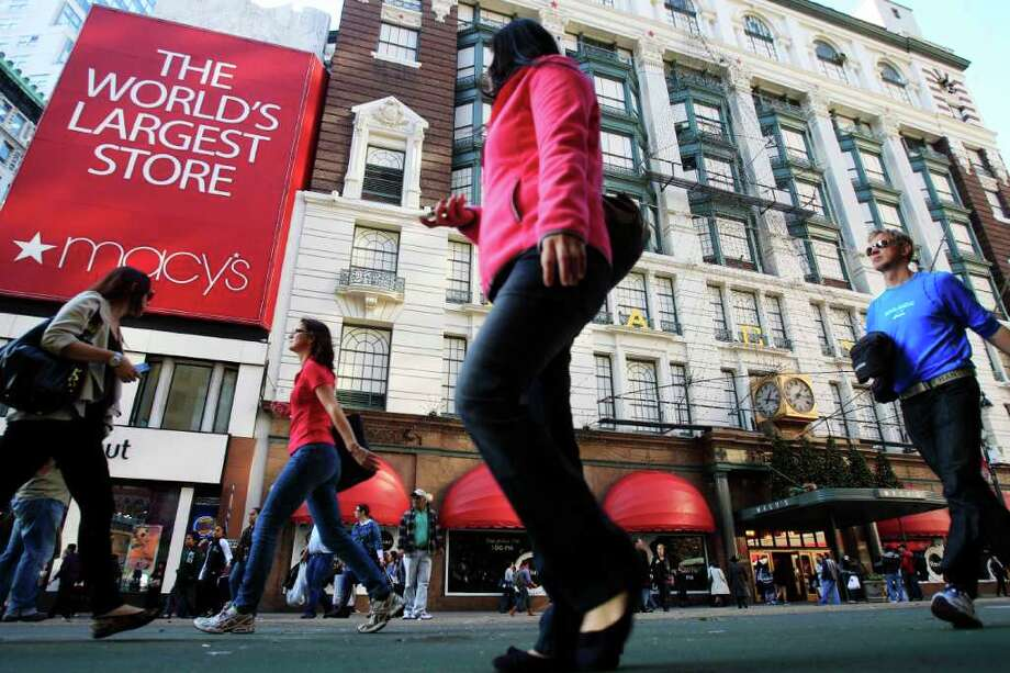 Pedestrians pass the Macy's department store location Nov. 8, 2011, in New York. Macy's Inc. is reporting Wednesday, Nov. 9, 2011, that earnings surged in the third quarter as the department store chain reaps the benefits from tailoring its merchandise to local markets (AP Photo/Frank Franklin II) Photo: Frank Franklin II / AP