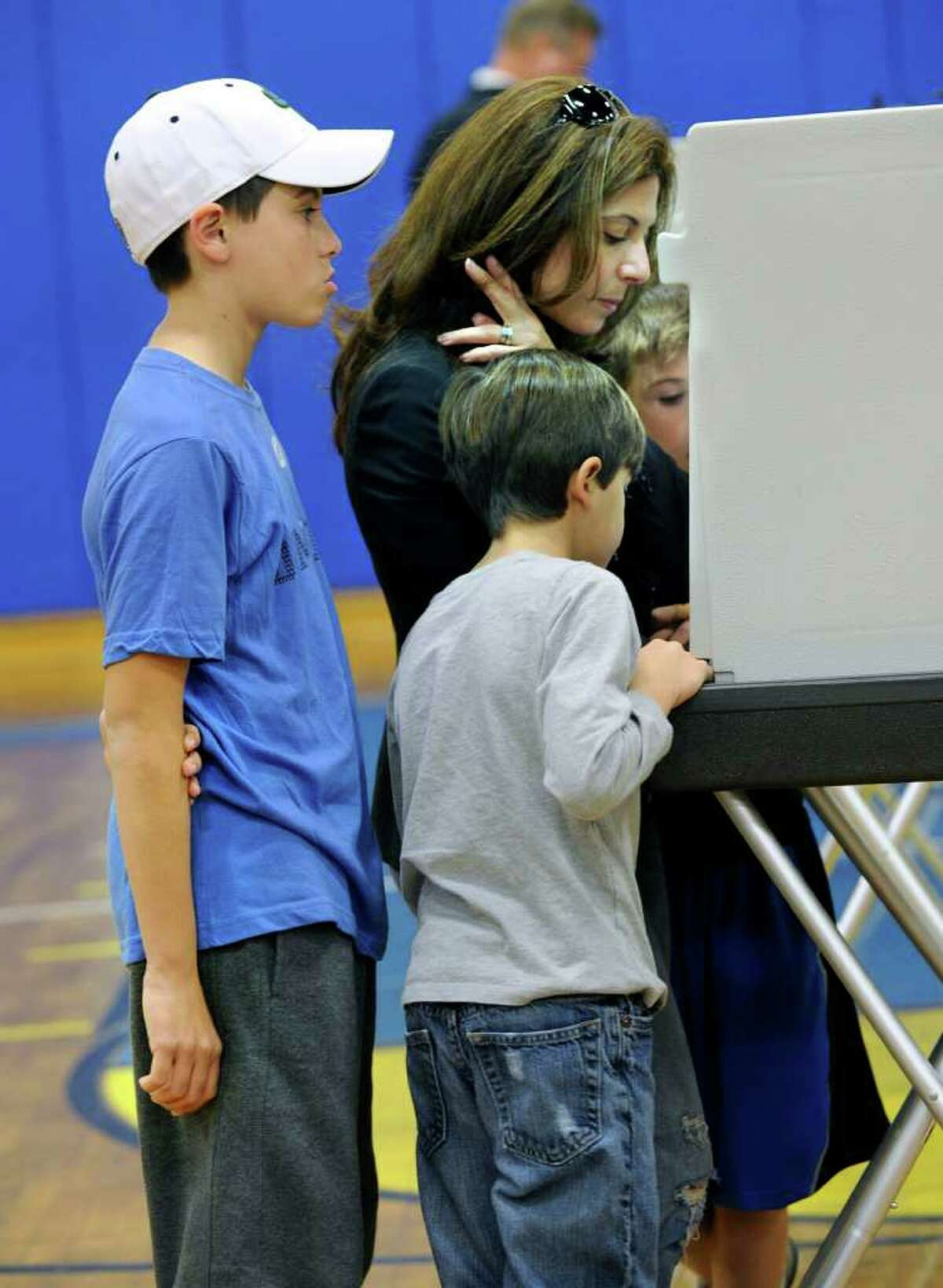 Diane Culhane, brought her sons with her to vote at the Brookfield High school polling place Tuesday. The boys are from left, Brenan, 12, Lucas, 7 and Jack, 9. Photo taken Tuesday, Nov. 8, 2011.