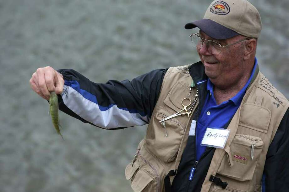 Randy Long of Fort Worth holds up his catch during the retreat at Joshua Creek Ranch. Photo: JERRY LARA, San Antonio Express-News / SAN ANTONIO EXPRESS-NEWS