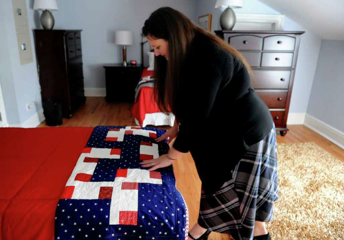 Lauren Cust, veteran and case manager at the Pfc. Nicholas A. Madaras Home for women veterans, smooths a quilt at the end of the bed in one of the rooms at the shelter. The quilt was hand-made by the BBT Quilt Guild in Bristol, Conn.