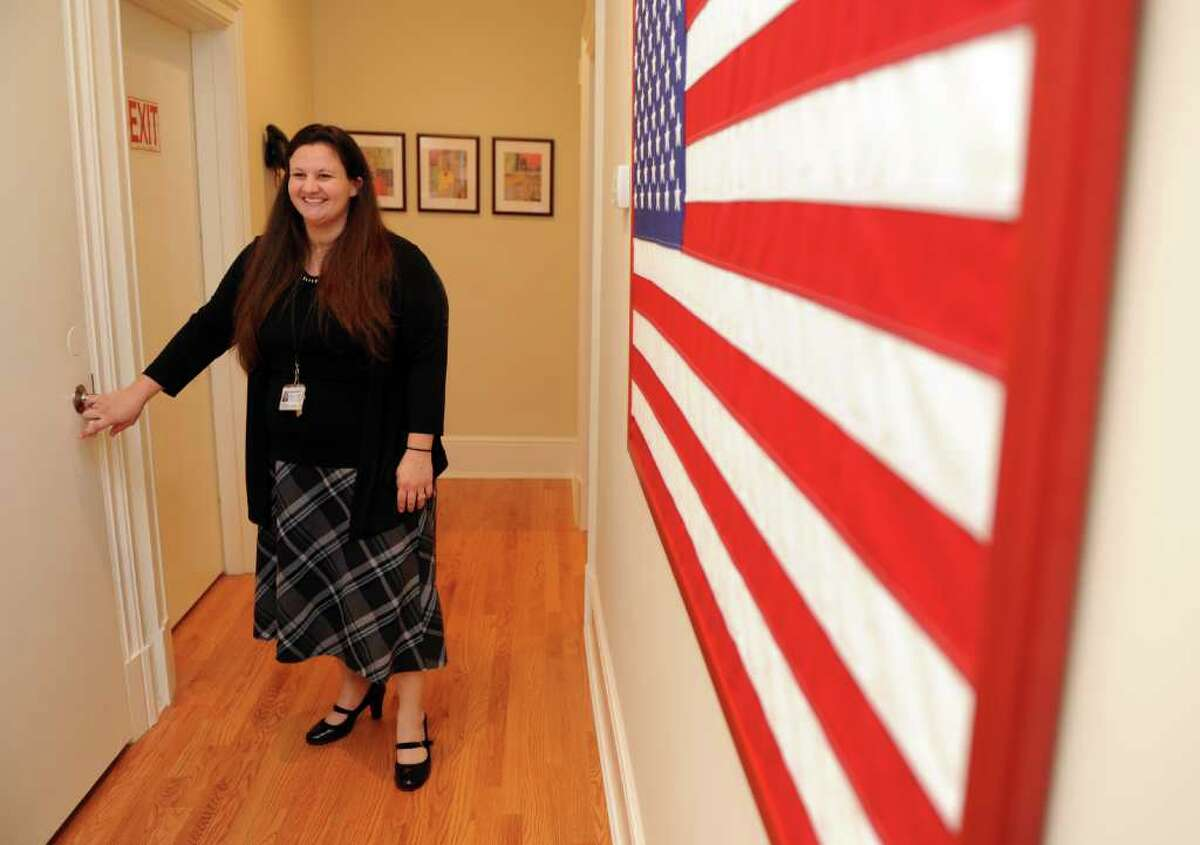 Lauren Cust, an Iraq War veteran and case manager at the Pfc. Nicholas A. Madaras Home for women veterans, walks through the hallway on the second floor of the home.