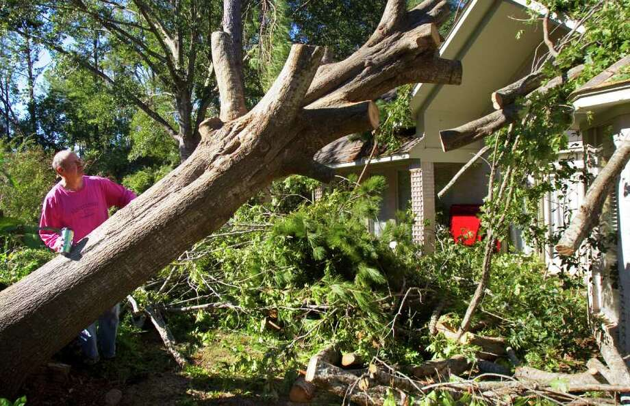"John Koch stands in his back yard as he looks at his tornado-damaged house Wednesday, Nov. 9, 2011, in Kingwood. ""I planted that tree 19 years ago when we moved in,"" Koch said. Photo: Cody Duty, Houston Chronicle / © 2011 Houston Chronicle"