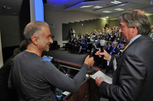 Dr. Alain E. Kaloyeros, Senior Vice President and Chief Executive Officer of the College of Nanoscale Science and Engineering, left, accepts the microphone from David M. Buicko, Chief Operating Officer of The Galesi Group and Chair of the CEG Board of Governors, right, before giving his keynote speech at the CEG Annual Meeting & 25th Anniversary at Albany Nanotech on Wednesday Nov. 9, 2011 in Albany, NY.  (Philip Kamrass / Times Union ) Photo: Philip Kamrass / 00015332A