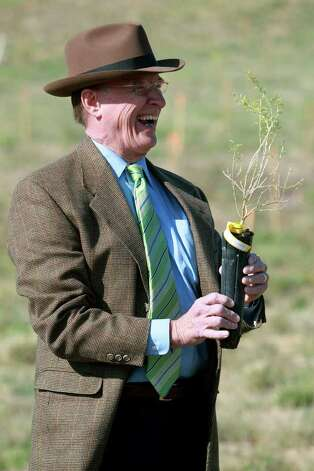 "County Judge Nelson Wolff gets a laugh out of handling a ""Wolfberry"" shrub as he  plants the first of over 3,000 trees and shrubs in Confluence Park on the San Antonio River Mission Reach Wednesday morning, November 9, 2011. Photo: TOM REEL, SAN ANTONIO EXPRESS-NEWS / © 2011 San Antonio Express-News"