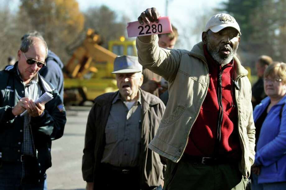 Musa Kabba of Brooklyn, right, holds up his number as his bid is made final during an auction on Wednesday, Nov. 9, 2011, at the New York State Thruway barn in Selkirk, N.Y. The Thruway Authority and Canal Corp. holds four auctions a year to sell old troop cars, machinery, trailers, plow wings, scrap metal, compressors and other miscellaneous items from across the state.  (Cindy Schultz / Times Union) Photo: Cindy Schultz / 00015325A