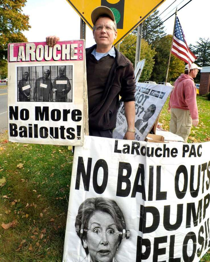 Bob Wasser of the LaRouche Political Action Committee displays protest signs to passing motorists in New Fairfield on Tuesday, Oct.20,2009. Photo: Michael Duffy / The News-Times