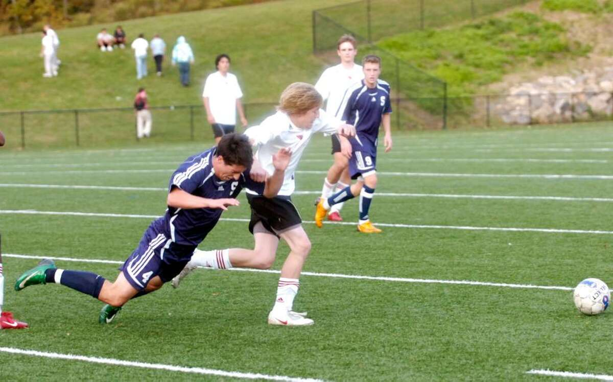 Greenwich's Matthew Wenger outruns Staples' Mike White as Greenwich hosts Staples in a boys soccer match. Staples won 3-0.
