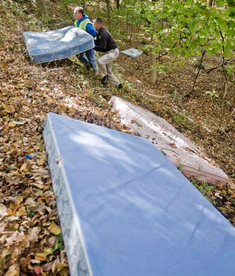 Chris McGran from the Highway Department and Shawn Stillman, coordinator for the Unified Neighborhood Inspection Team bring up illegally dumped mattresses on Brushy Hill Road. Wednesday, Oct. 14, 2009 Photo: Scott Mullin / The News-Times