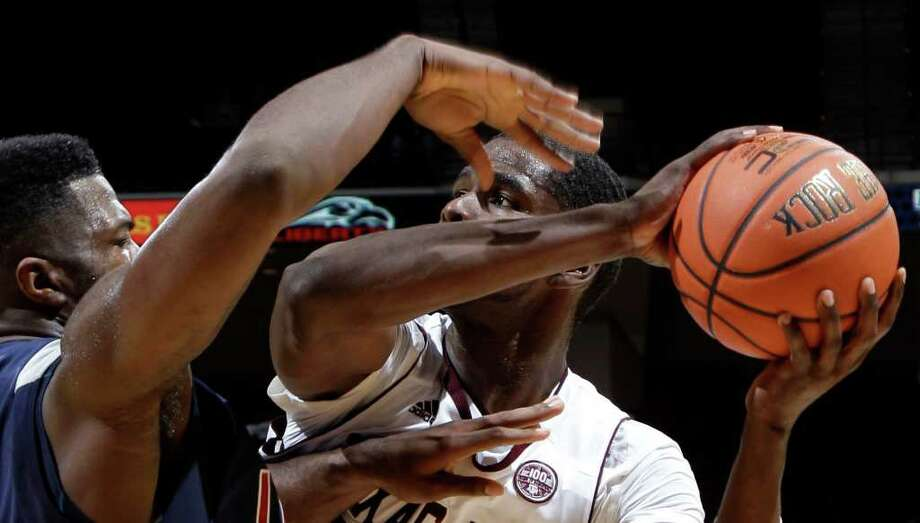 DAVID J. PHILLIP : ASSOCIATED PRESS BALL SKILLS: Texas A&M's Ray Turner, right, keeps the ball from Liberty's Antwan Burrus in the Aggies' 81-59 victory. Photo: David J. Phillip / AP