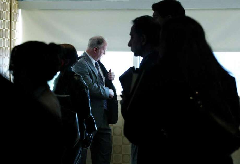 FILE - In this Oct. 17, 2011 file photo, a man pauses by a window as job seekers wait to get information and drop off resumes during a job fair in Boston. Applications for unemployment benefits fall to 390,000 Thursday, Nov. 10, 2011, lowest level since mid-April. (AP Photo/Elise Amendola, File) Photo: Elise Amendola / AP2011