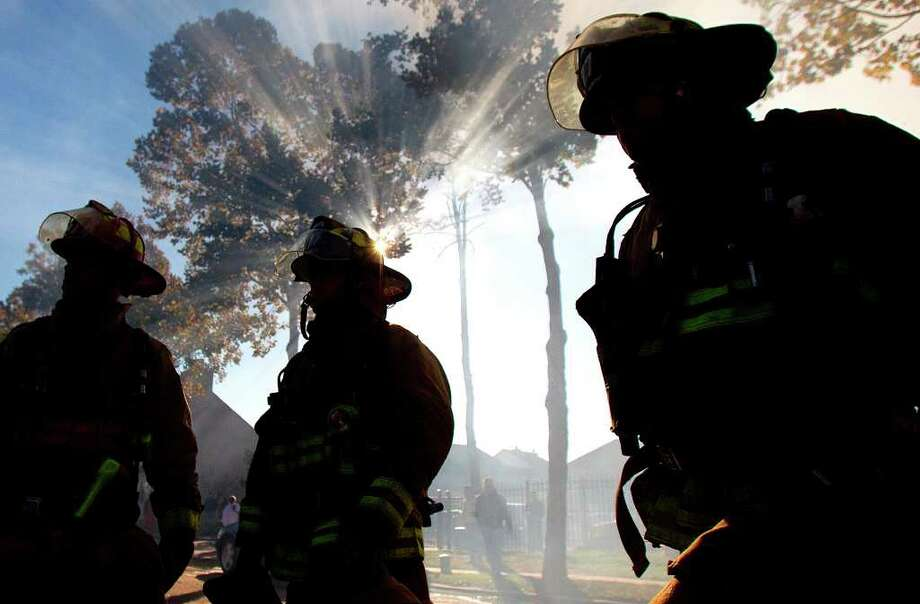Firefighters take a break after working to extinguish a blaze at the Sterling Crossings apartment complex in the 4600 block of South Kirkwood Rd., Thursday, Nov. 10, 2011, in Houston. Photo: Cody Duty, Houston Chronicle / © 2011 Houston Chronicle
