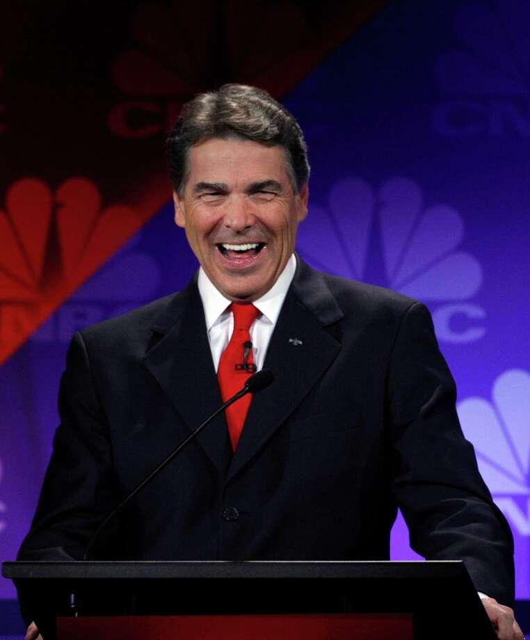Republican presidential candidate Texas Gov. Rick Perry laughs during a Republican Presidential Debate at Oakland University in Auburn Hills, Mich., Wednesday, Nov. 9, 2011.  (AP Photo/Paul Sancya) Photo: Paul Sancya, STF / AP