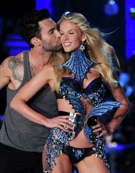 Adam Levine, lead singer of the group Maroon 5, kisses model Anne Vyalitsyna as she presents a creat