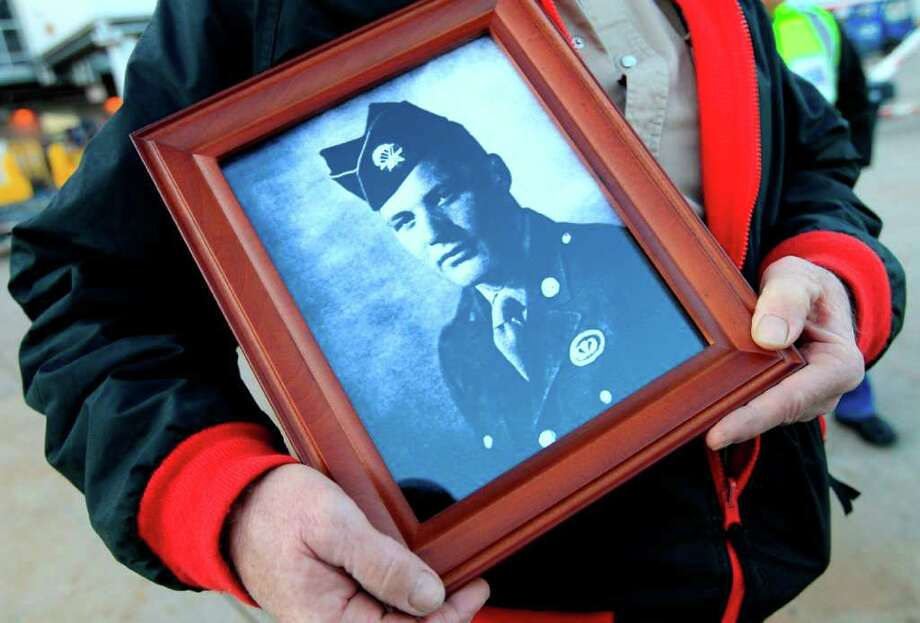 Benny Don Wherley of Blossom, Texas, holds a portrait of his uncle, Sgt. 1st Class Benny Rogers after the remains of Sgt. Rogers arrived at Dallas-Fort Worth International Airport Thursday, Nov. 10, 2011, in Grapevine. The remains of the Korean War veteran from East Texas have been returned to his family more than 60 years after he was declared missing in action. Photo: Tony Gutierrez, Associated Press / AP
