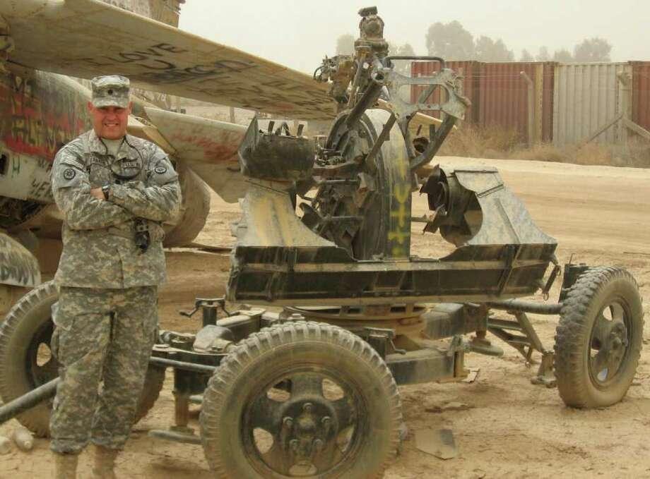 Lt. Col. Richard Franzis stands beside the base of an anti-aircraft gun in the Iraq desert. Photo: Contributed Photo / Westport News