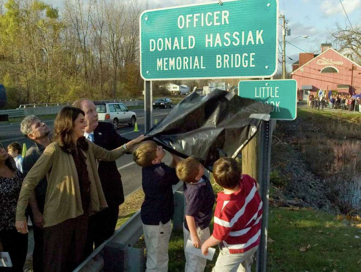 Members of the Hassiak family remove the cover revealing the sign memorializing Donald Hassiak along Route 7 in New Milford on Thursday, Nov. 10, 2011. Donald, a Danbury police officer, was the family patriarch and was killed in a hit-and-run accident while biking to work on June 3, 2010. The Hassiak family from left: Kimberly Duff Hassiak, and sons Matthew, 9; D.J., 6; and Luke, 8.
